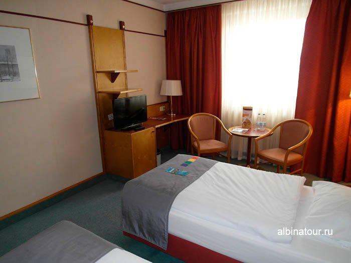 На столе телевизор и настольная лампа в номере отеля Парк Инн