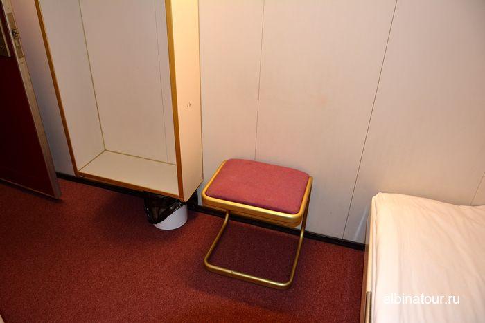 Открытый шкаф и банкетка в каюте на пароме Анастасия